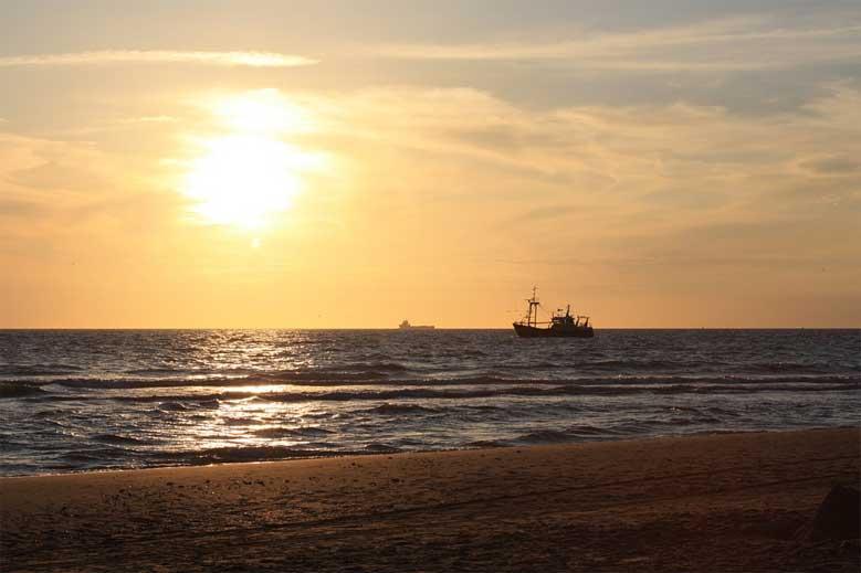 Schiff im Licht der untergehenden Sonne vor der Küste